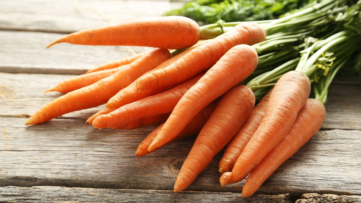 bunch of carrots on a grey wooden table