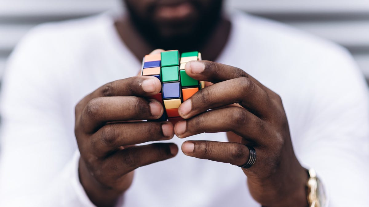 closeup of man's hands using a Rubik's Cube