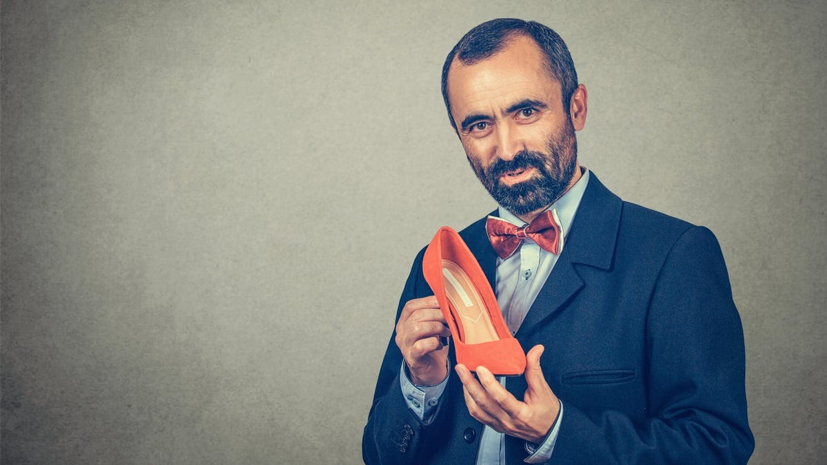 Businessman holding one red high heel shoe looking at camera