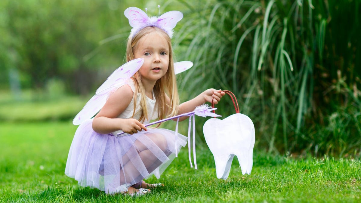 little girl in tooth fairy costume in a park holding tooth-shaped bag