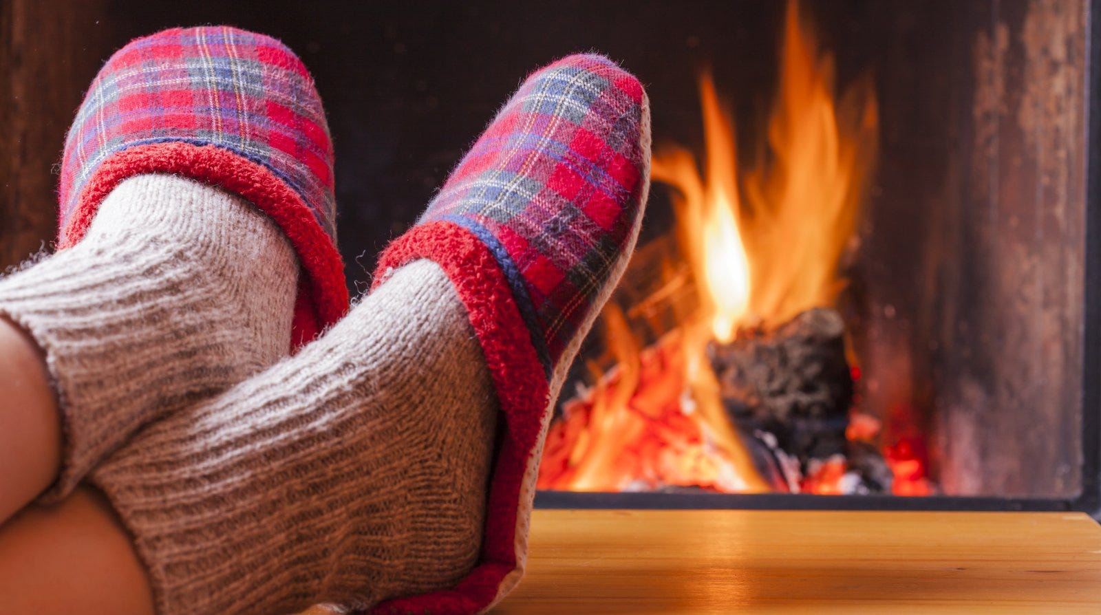closeup of feet wearing slippers propped in front of a fireplace
