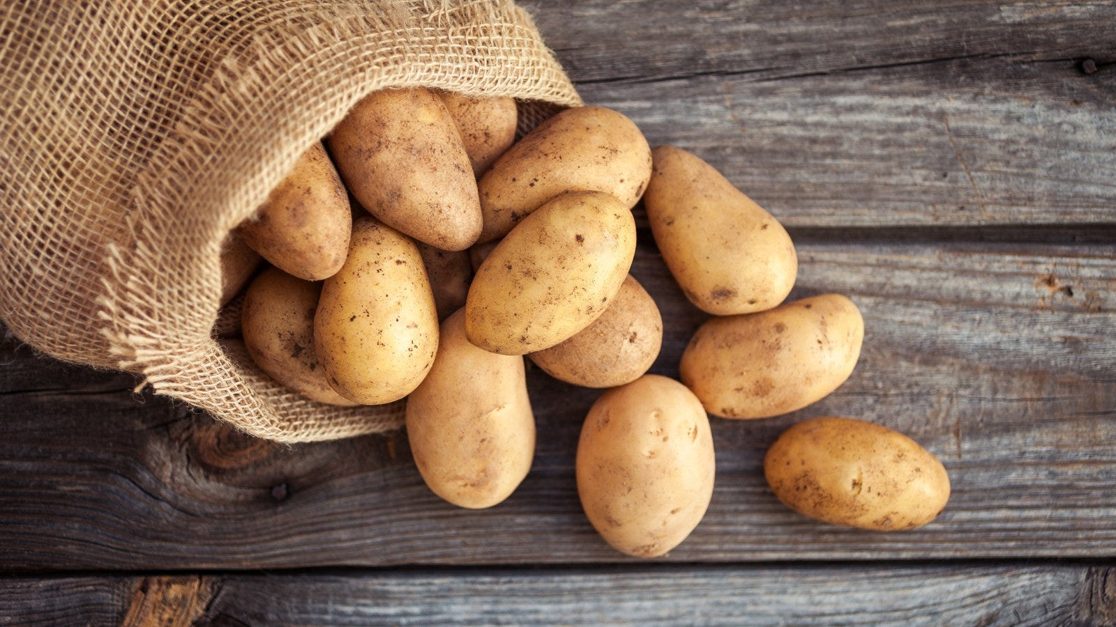 Fresh potatoes in an old sack on wooden background