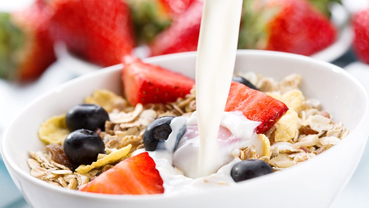 milk pouring into bowl of cereal with fresh berries