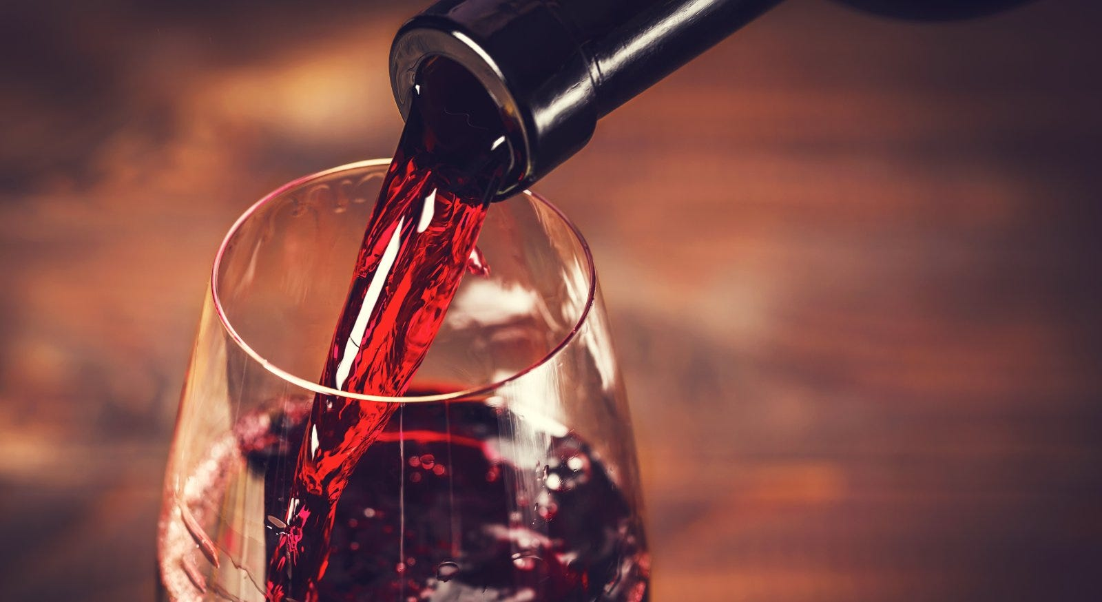 Pouring red wine into a glass against a wooden background