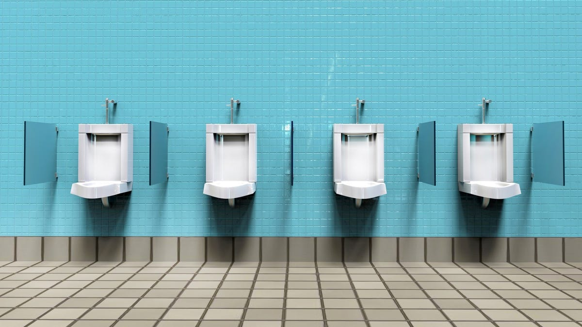 Men's room with white porcelain urinals in line