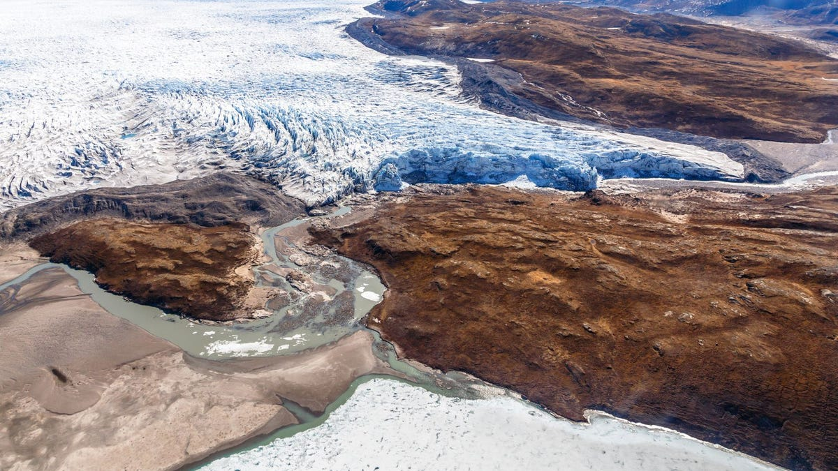 Greenlandic ice sheet melting glacier into river with tundra aerial view