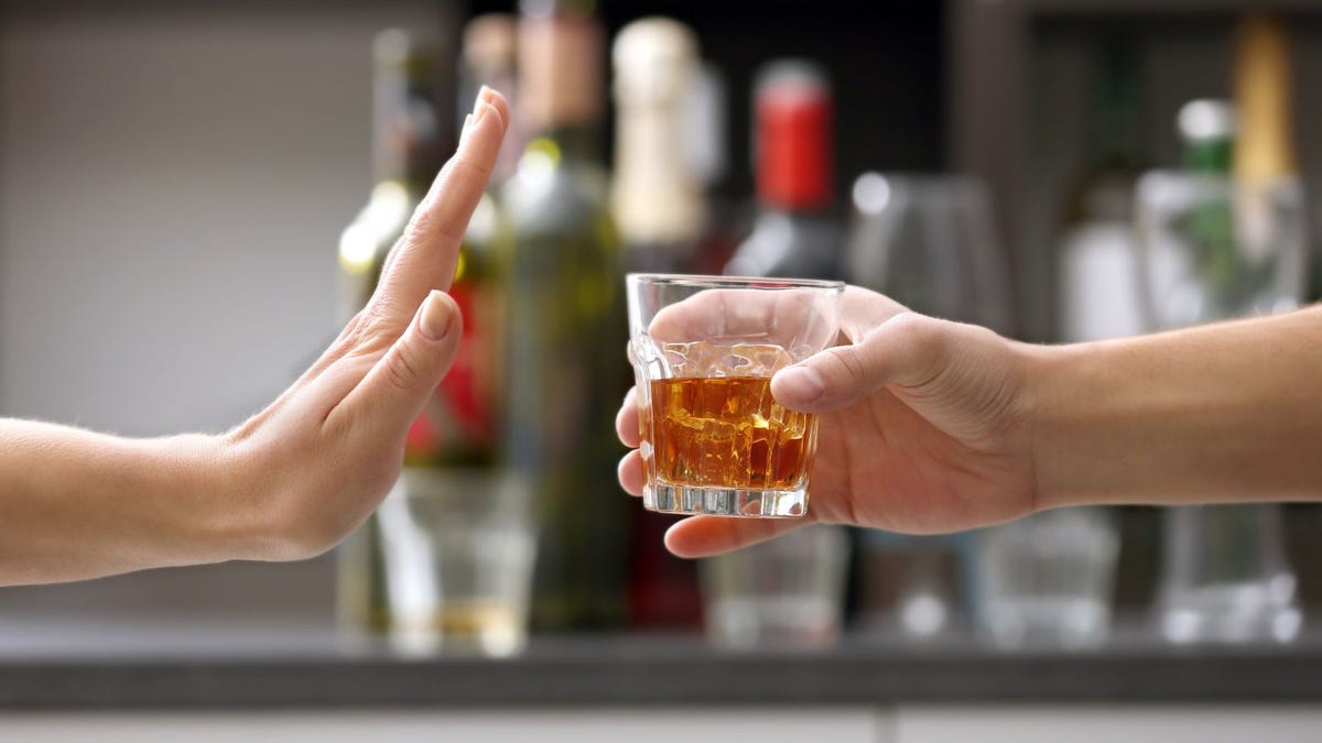 Female hand rejecting glass with alcoholic beverage