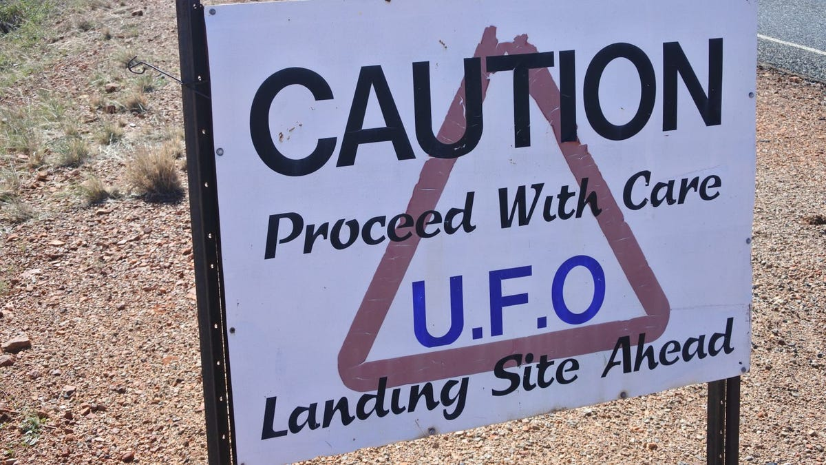 Sign stating proceed with care: UFO landing site ahead