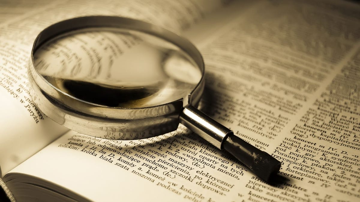 magnifying glass resting on open dictionary