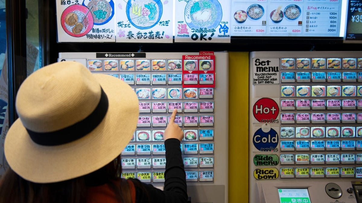 A woman buying hot a Japanese noodle dish from a vending machine
