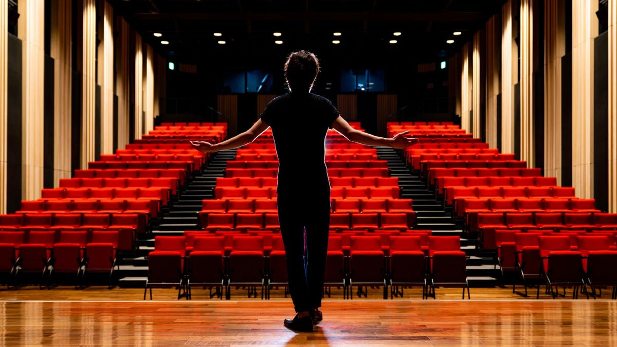 Young actor on stage in front of empty theater