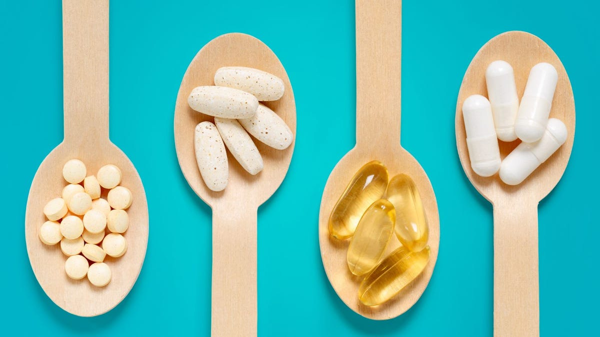 Healthy supplements on wooden teaspoons against pastel blue background