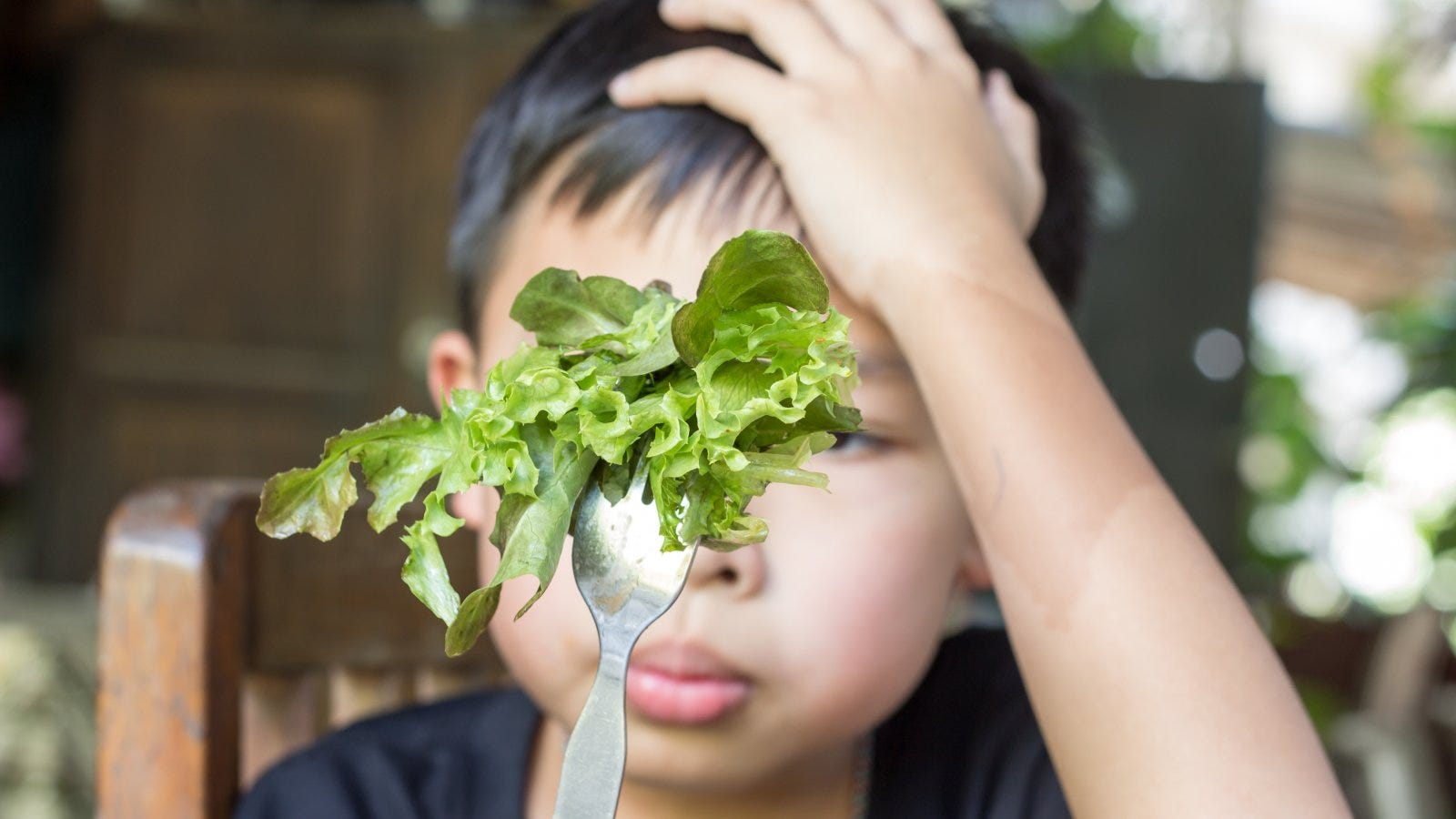 child staring unhappily at salad on a fork