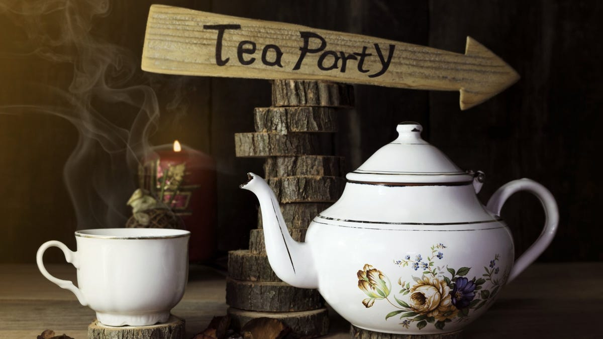 Cup of Tea and Teapot On Wooden Table With tea party Sign in the Background