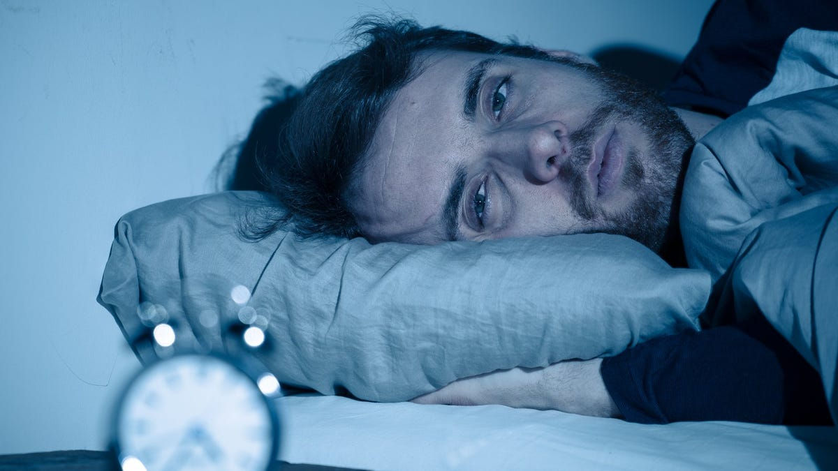sleepless man awake in bed with alarm clock in foreground
