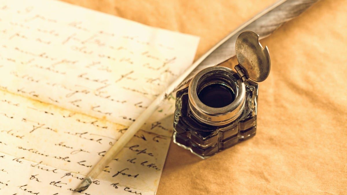 quill pen and ink bottle next to manuscript on parchment