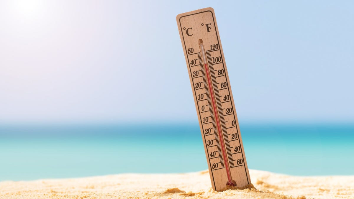 Thermometer sticking out of sand on beach and Showing High Temperature