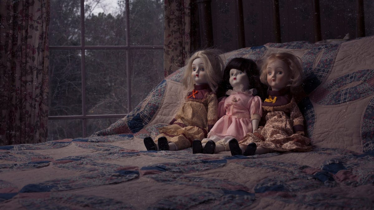 Creepy dolls on a bed