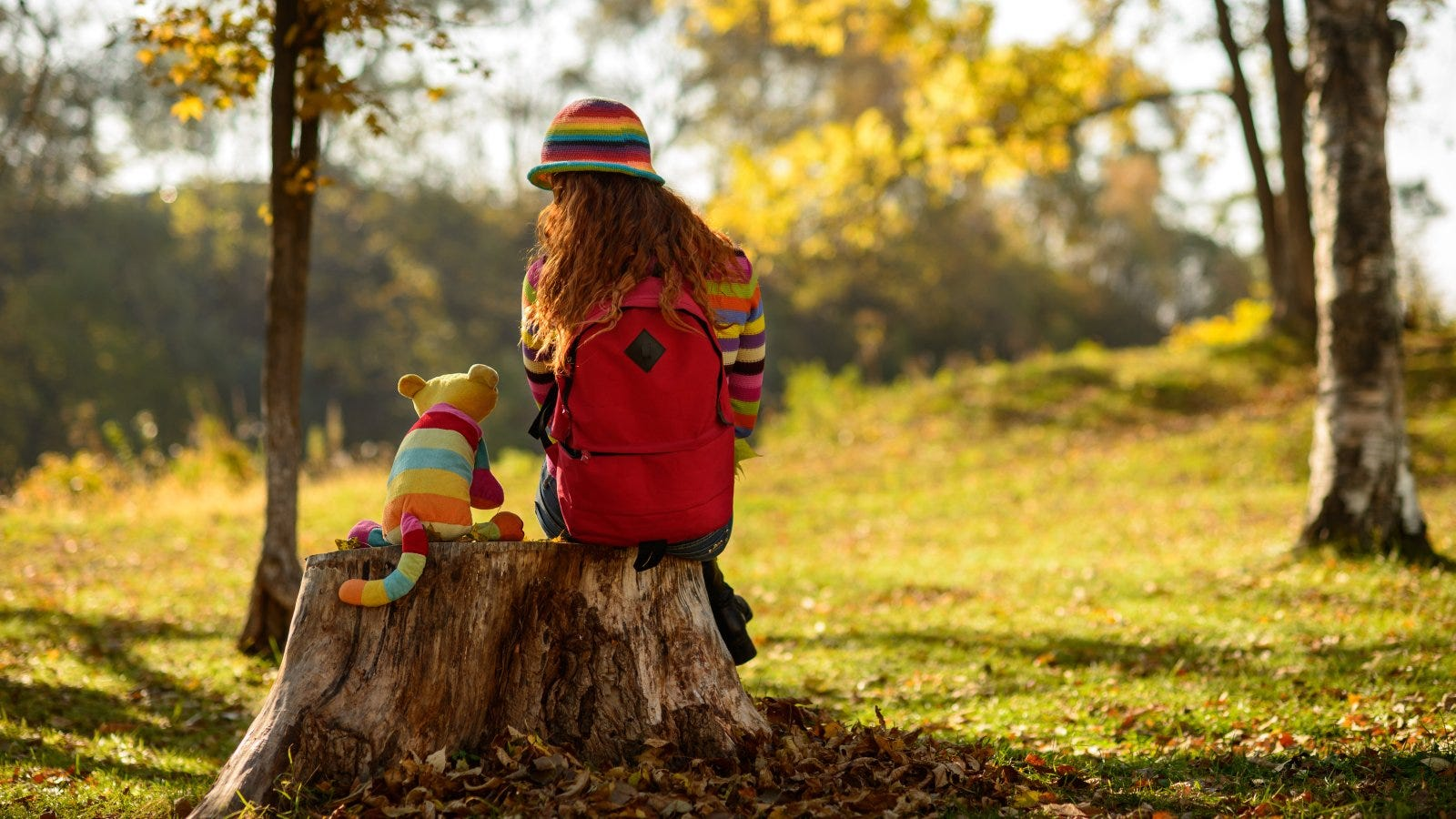 young redhead girl sitting on stump with her toy cat