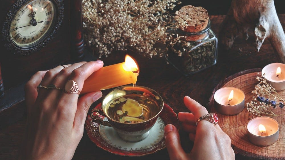 woman's hands dripping candle wax into ornate teacup
