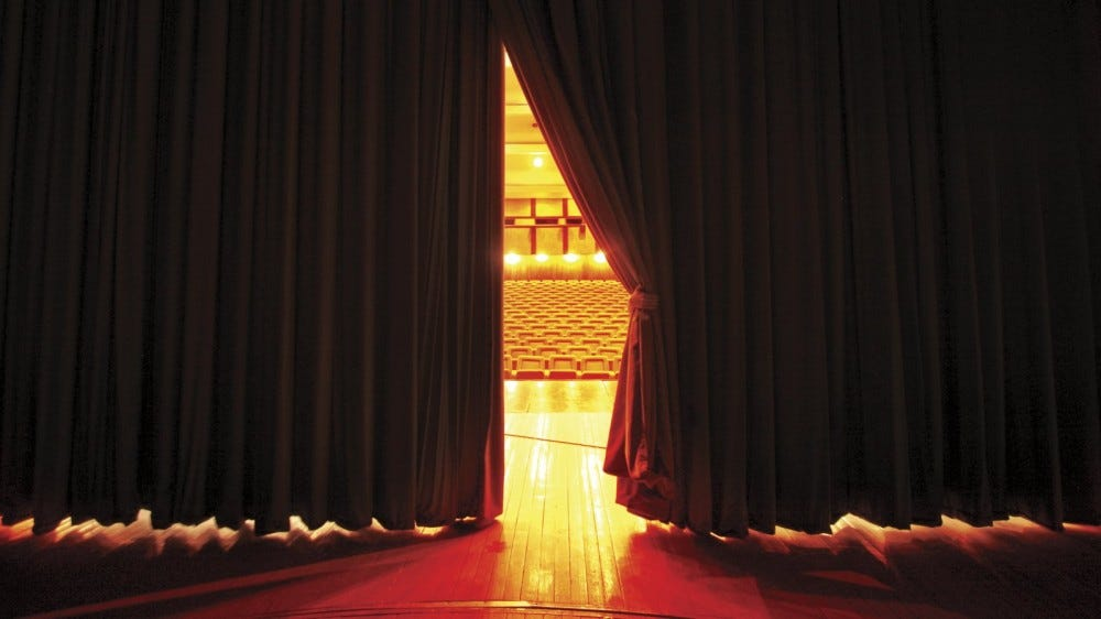 looking at theater seats from backstage through parted curtains