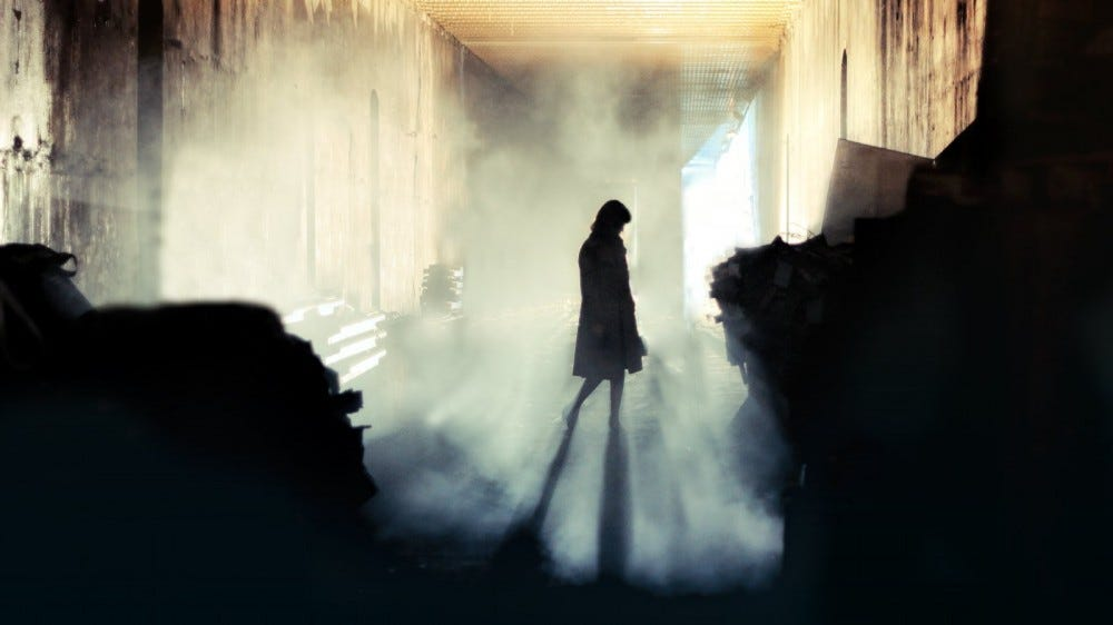 Silhouette of woman in misty alleyway
