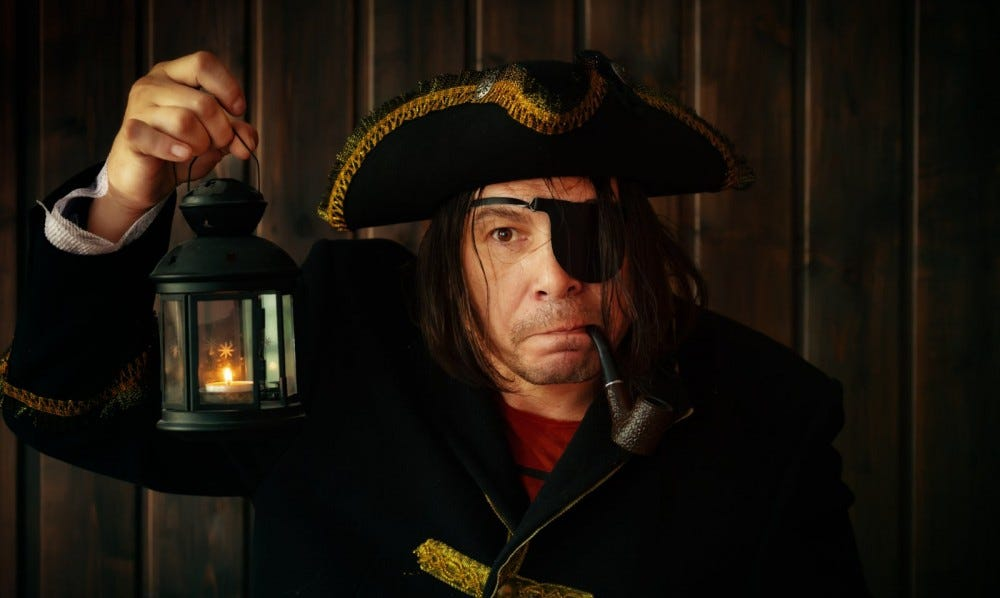 Portrait of a medieval pirate wearing eye patch and holding lantern