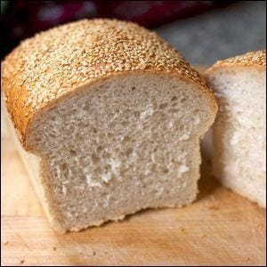 A loaf of white bread with a sesame seed top crust.