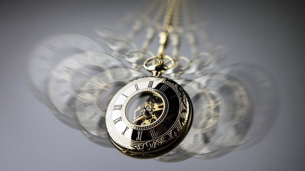 Gold pocket watch blurred while swinging back and forth