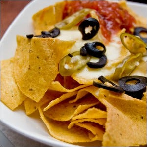 A plate of tortilla chips topped with melted cheese, sliced chile peppers, sliced black olives, and chili sauce.