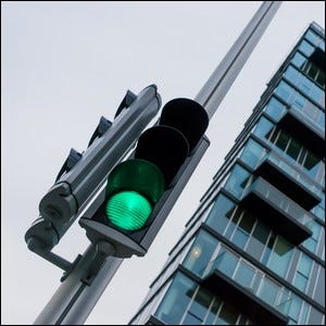 A building and traffic light at a city intersection.