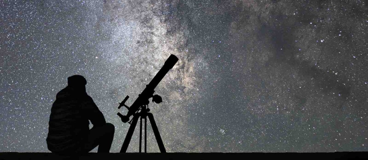 silhouette of man and telescope against starry night sky