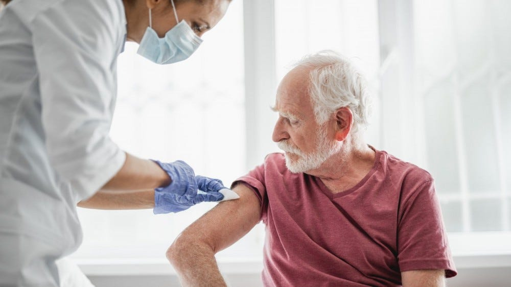 Older bearded man receiving flu vaccine from nurse