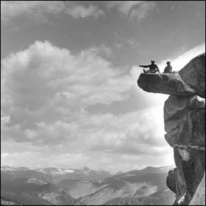 A photograph of A.E. McConnell and his daughter sitting on the precarious Glacier Point in Yosemite National Park, 1901.