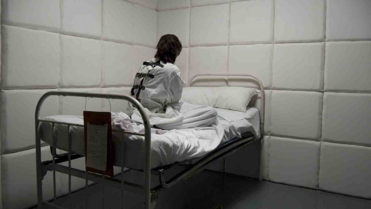 woman in straightjacket in padded room of asylum