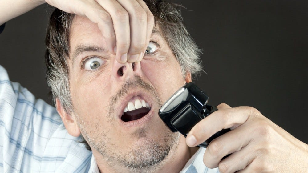 Close-up of a man attempting to trim his nose hair with a full sized electric razor