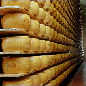 A cheese aging storeroom with hundreds of wheels of cheese stacked up on shelves.