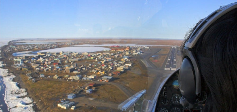 Pilot of a small airplane flies over the whaling village of Barrow