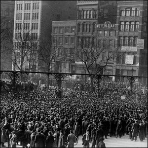 A large crowd gathered in Union Square around a speaker's platform, near the Mehlin Piano building.
