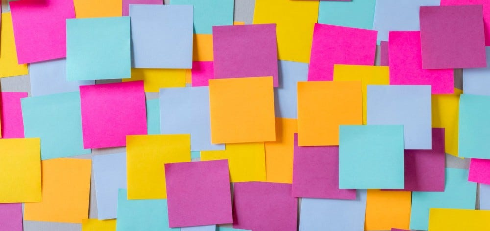 many color sticky notes on a wall