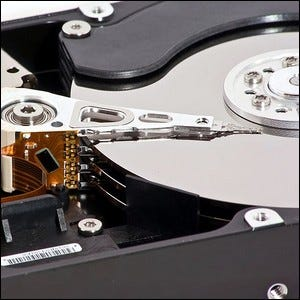 An open hard drive showing the physical platters and actuator arm.