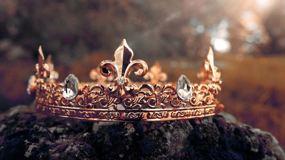 gem-encrusted gold crown sitting on moss-covered stone in misty field