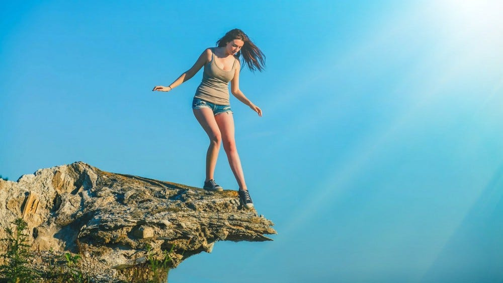 woman stands at the top of a cliff edge looking fearful