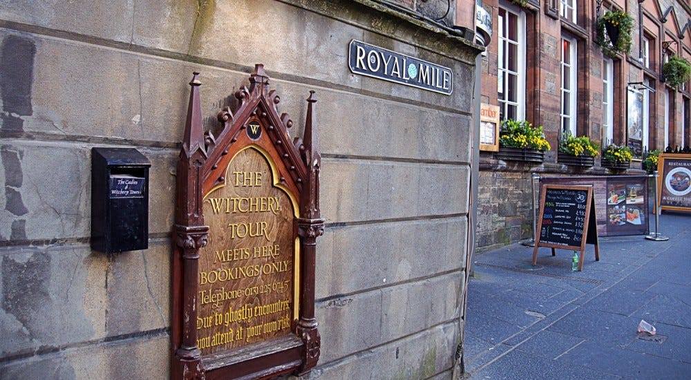 Ornate sign on brick wall marking the beginning point of Witchery tour on the Royal Mile
