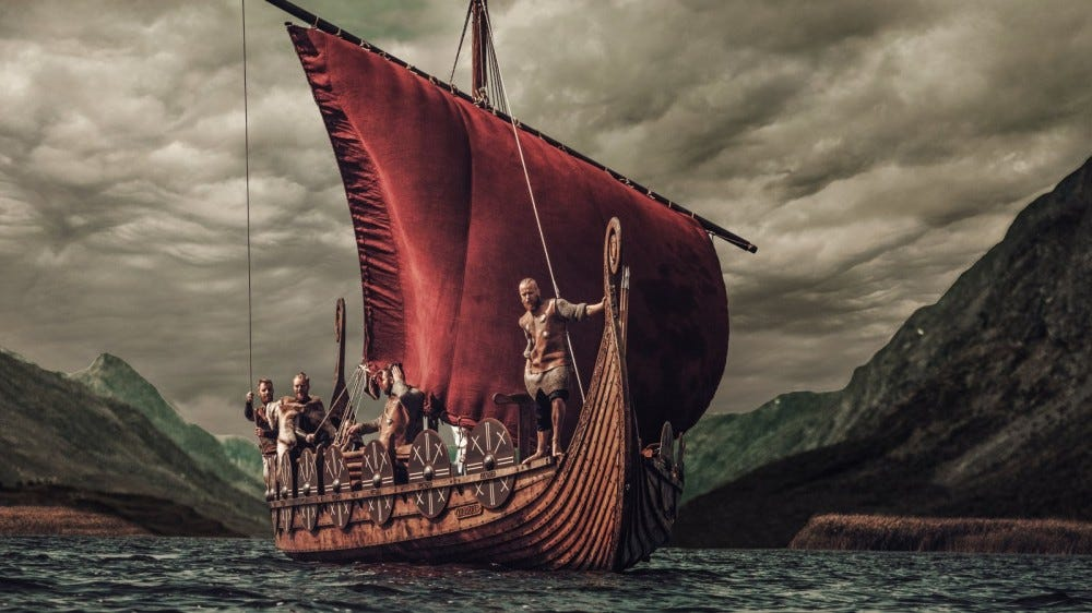Group of Vikings are floating on the sea on a longship with mountains on the background