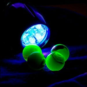 Uranium glass marbles glowing in front of a UV flashlight at night.