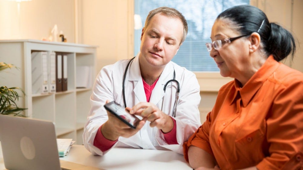 Male doctor holding digital tablet, showing test results to woman in clinic
