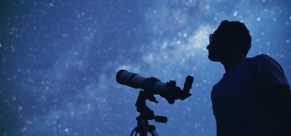 silhouette of astronomer and telescope against night sky