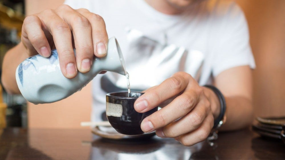 Close up of a man pouring Japanese sake in a porcelain cup