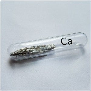 A mineral sample of pure calcium in a glass container.